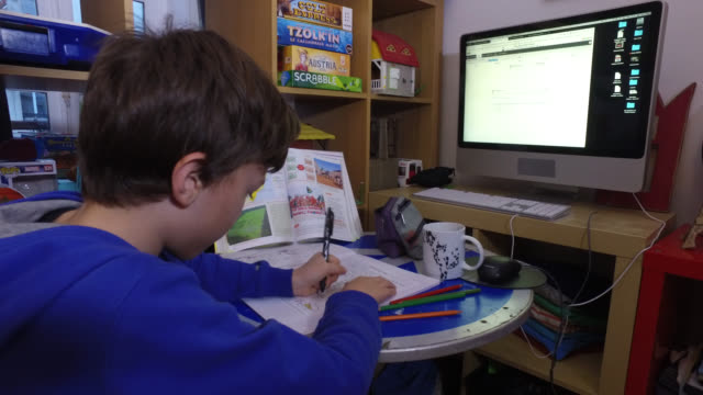 an 11yearold with his notebooks and schoolbooks in front of a computer president macron announced on monday march 16 that the fight against... - homework stock videos & royalty-free footage
