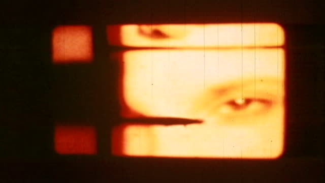 stockvideo's en b-roll-footage met an 8mm sprocket-holed piece of film of a young woman's eyes is pierced. - sprocket