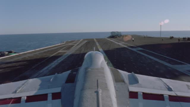 an a-6 intruder lands on an aircraft carrier on the ocean. - flugzeugträger stock-videos und b-roll-filmmaterial