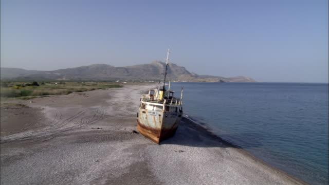 stockvideo's en b-roll-footage met an abandoned, beached industrial boat lies near the shore on the island of rhodes, greece. - scheepswrak