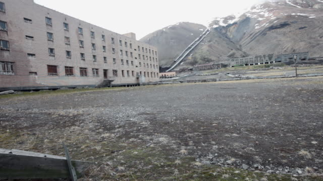 an abandoned building with seagulls nesting on the windows and an old mine in the background, pyramiden, a soviet ghost town on the archipelago of svalbard - 1927 stock videos & royalty-free footage