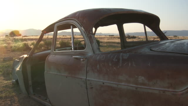 an abandoned car sits in the namib desert. - scrap yard stock videos & royalty-free footage