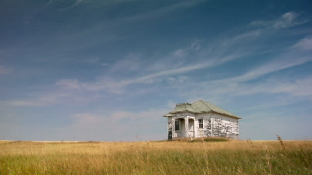 An abandoned farmhouse occupies a wide grassy field in North Dakota.