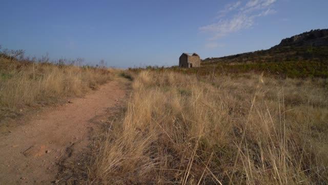 vídeos y material grabado en eventos de stock de an abandoned house is seen near a path, in a field, near the gozzi mount, on september 19, 2020 in corsica, france. - carretera de tierra