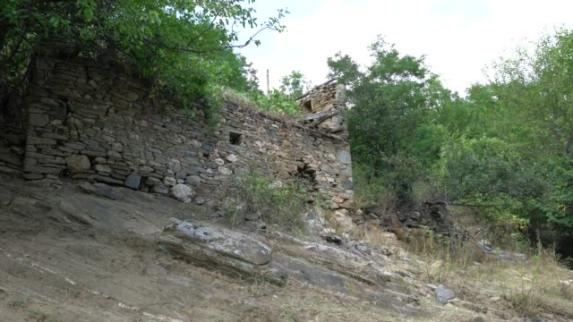 an abandoned stone house in a village in eastern rhodope mountains in bulgaria - stone house stock videos & royalty-free footage