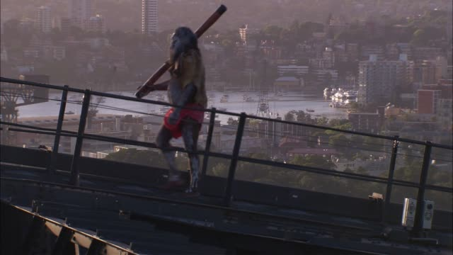 an aboriginal man carrying a pole walks up an incline on the sydney harbor bridge. - indigenous peoples of the americas stock videos & royalty-free footage