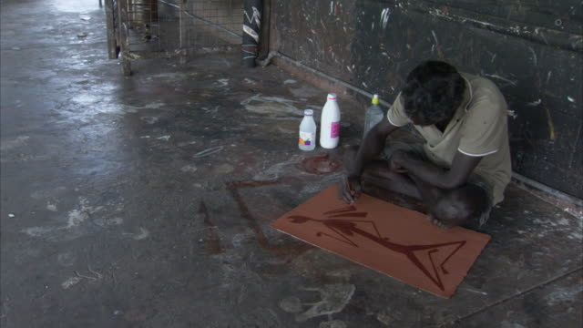 An Aboriginal man sits on a floor and paints on a canvas.
