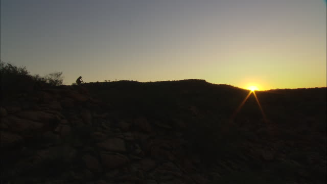 an aboriginal man stands on a rock far in the distance and plays didgeridoo during sunset. - aboriginal australian ethnicity stock videos & royalty-free footage