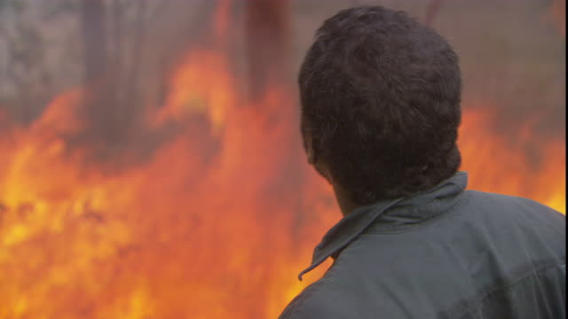 an aboriginal man watches a brush fire in the outback. - aboriginal australian ethnicity stock videos & royalty-free footage