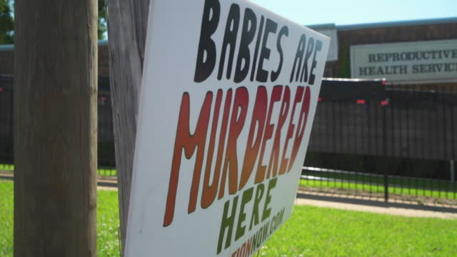 an abortion clinic in alabama with anti-abortion posters outside - clinic stock videos & royalty-free footage
