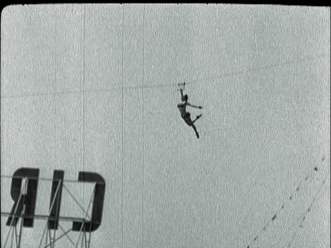 montage an acrobat sliding down a high wire via pulley above venice ocean amusement park / santa monica, california, united states - gliding stock videos and b-roll footage