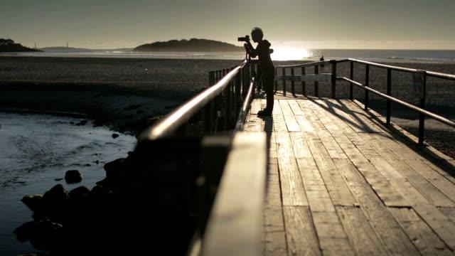 vídeos de stock e filmes b-roll de an active female pensioner photographs in the first dawn - equipamento fotográfico