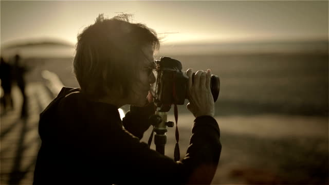 An active female pensioner photographs in the first dawn