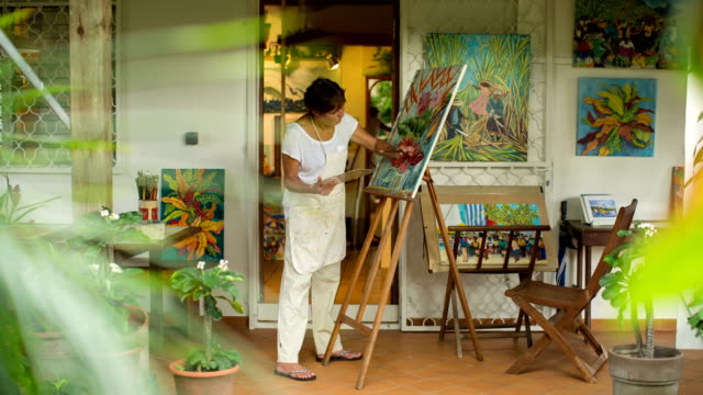 an active female senior paints pictures in her art studio - malen stock-videos und b-roll-filmmaterial