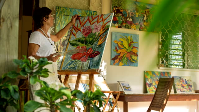an active female senior paints pictures in her art studio - staffelei stock-videos und b-roll-filmmaterial