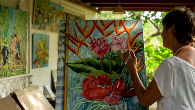 An active female senior paints pictures in her art studio