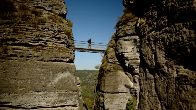 An active senior is hiking in the Elbe Sandstone Mountains in Saxonian Switzerland near Dresden