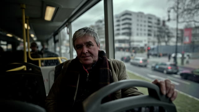 An active senior man drives in a double-decker bus across the Kurf��rstendamm in Berlin