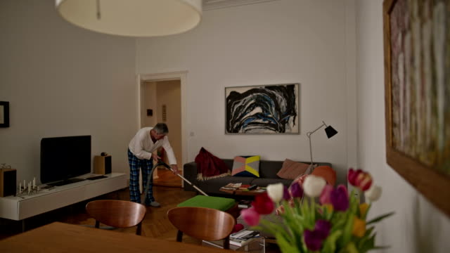 an active senior man during vacuum cleaning in his old berlin apartment - modern manhood stock videos & royalty-free footage