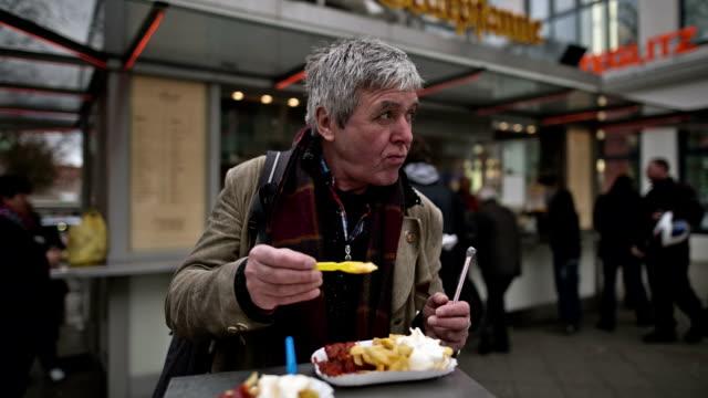 An active senior man enjoys an original Berlin Currywurst