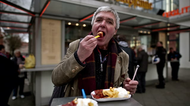 vídeos de stock e filmes b-roll de an active senior man enjoys an original berlin currywurst - berlim