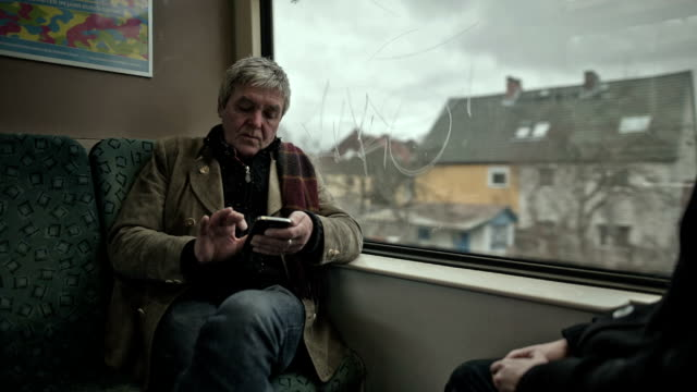 An active senior man is sitting in a moving Berliner S-Bahn train and typing into his smartphone