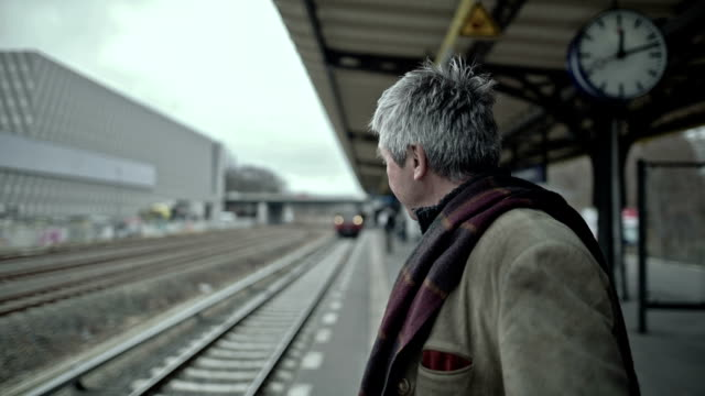 an active senior man is waiting for his train in a berlin s-bahn station - männliche person stock-videos und b-roll-filmmaterial
