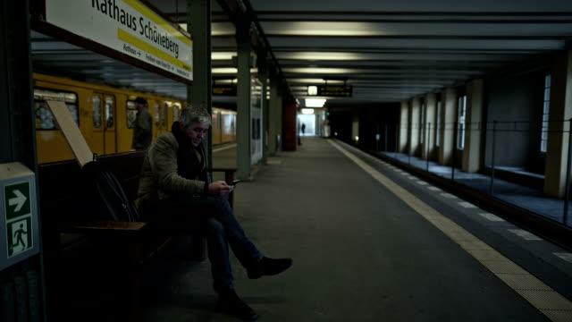 vídeos de stock, filmes e b-roll de an active senior man is waiting in a berlin subway station for his train and typing into his smartphone - estação de metrô