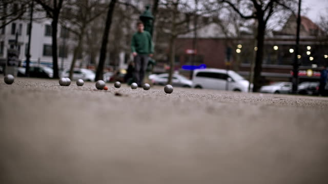 An active senior man plays boules in a side street near the Kurf������rstendamm in Berlin
