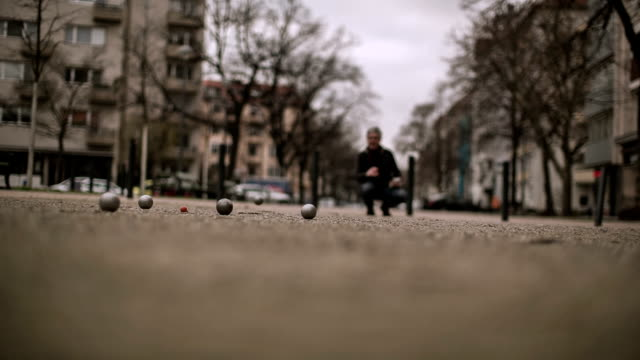 an active senior man plays boules in a side street near the kurf������rstendamm in berlin - nordeuropäischer abstammung stock-videos und b-roll-filmmaterial
