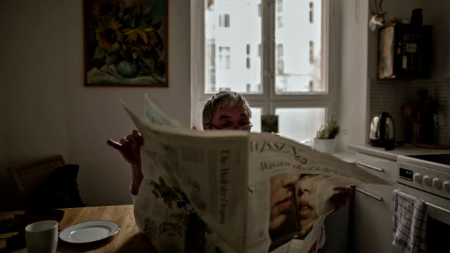 An active senior man reads his morning newspaper over a cup of coffee