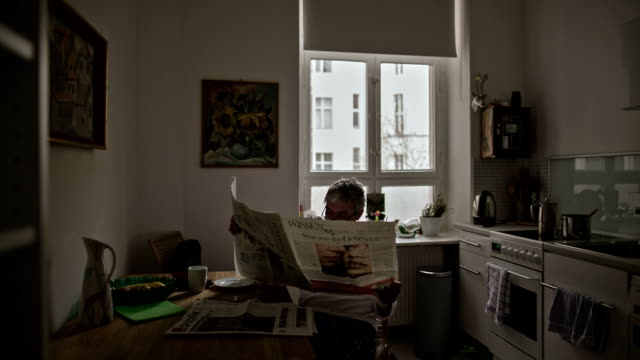 stockvideo's en b-roll-footage met an active senior man reads his morning newspaper over a cup of coffee - krant