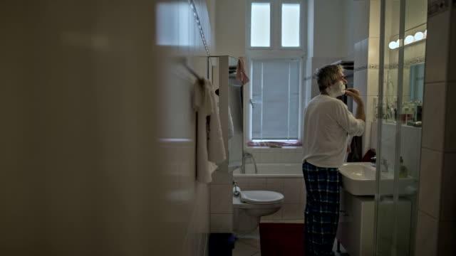 An active senior man shaving his face in bathroom