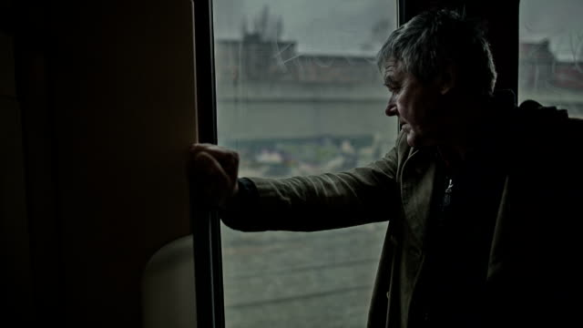 an active senior man stands at the door of a moving berlin s-bahn train while driving through berlin - nordeuropäischer abstammung stock-videos und b-roll-filmmaterial