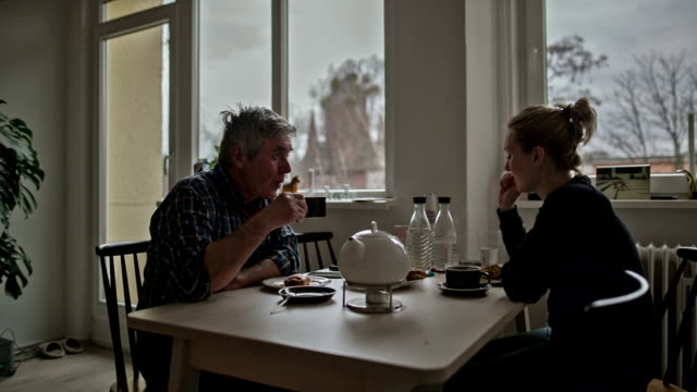 An active senior man with his attractive young daughter during the five o'clock tea