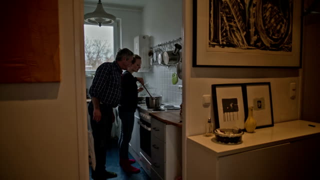 an active senior man with his attractive young daughter during cooking - real people stock videos & royalty-free footage