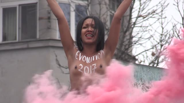An activist from the Femen women's rights movement protested on a Soviet era monument in the center of Kiev on Tuesday to mark the 100th anniversary...