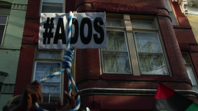 An activist holds up a hangman's noose during a protest to mark the National Reparations Day outside the residence of US Senate Majority Leader Sen...