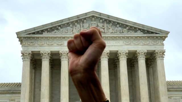 vidéos et rushes de an activist holds up her fist during a protest against the nomination of supreme court judge brett kavanaugh to the us supreme court in front of the... - fist