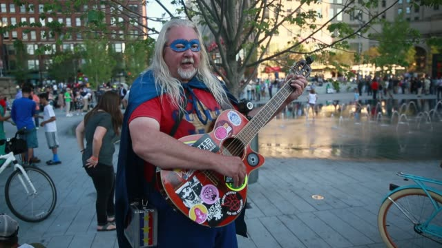 an activist plays a folk song in public square on the third day of the 2016 republican national convention in downtown cleveland - republikanischer parteitag stock-videos und b-roll-filmmaterial