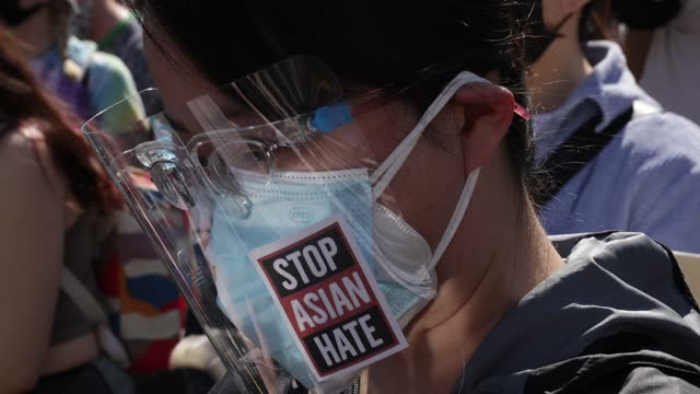 """an activist wears a faces shield with """"stop asian hate"""" sticker on it as activists participate in a """"dc rally for collective safety - protect... - pacific islanders stock videos & royalty-free footage"""