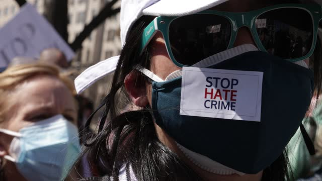 "an activist wears a ""stop hate crime"" sticker as activists chant and listen to a speaker in a ""dc rally for collective safety - protect asian/aapi... - social justice concept stock videos & royalty-free footage"
