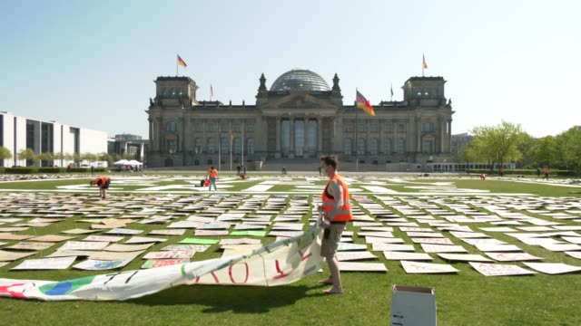 vídeos y material grabado en eventos de stock de an activist with the fridays for future movement helps to pin thousands of protest signs and banners to the lawn in front of the reichstag during the... - centro de berlín