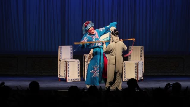 An actor and actress perform a Qinqiang Opera skit at a theater.