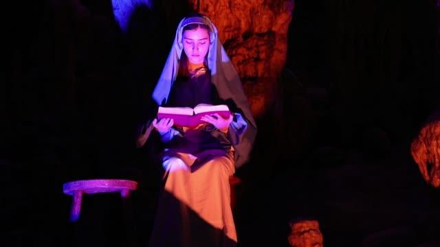 an actor dressed as mary perform live biblical scene in postojna cave on december 25 2018 in postojna slovenia the annual nativity scene is the... - avvenimento biblico video stock e b–roll