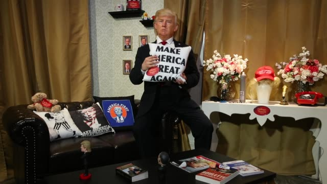 vídeos de stock e filmes b-roll de an actor wearing a silicon mask in the likeness of us president donald trump poses with a boxing bag adorned with a picture of german chancellor... - equipamento doméstico