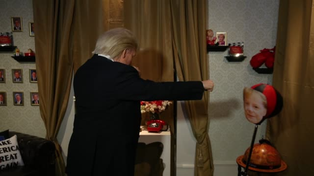 an actor wearing a silicon mask in the likeness of us president donald trump poses with a boxing bag adorned with a picture of german chancellor... - angela merkel stock videos & royalty-free footage