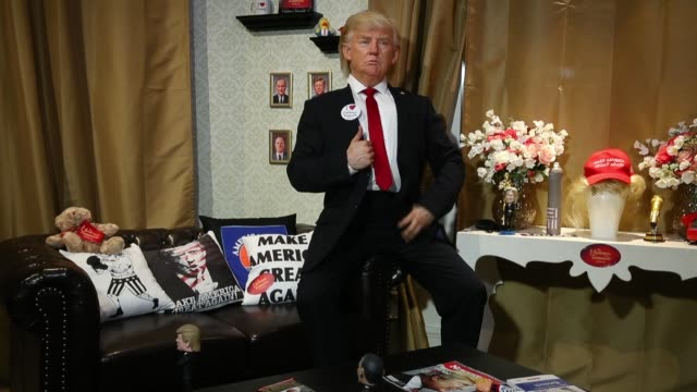 an actor wearing a silicon mask in the likeness of u.s. president donald trump poses with a boxing bag adorned with a picture of german chancellor... - raw footage stock videos & royalty-free footage