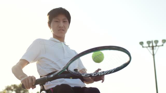 彼のラケットを使用して地面からテニスボールを選ぶ適応アスリートのslo mo cu - スポーツ用語点の映像素材/bロール