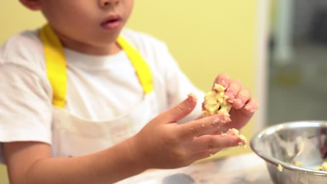 vídeos de stock, filmes e b-roll de um garoto adorável asiático aprende para cozinhar, preparando uma padaria na cozinha. - artigo de vestuário para cabeça
